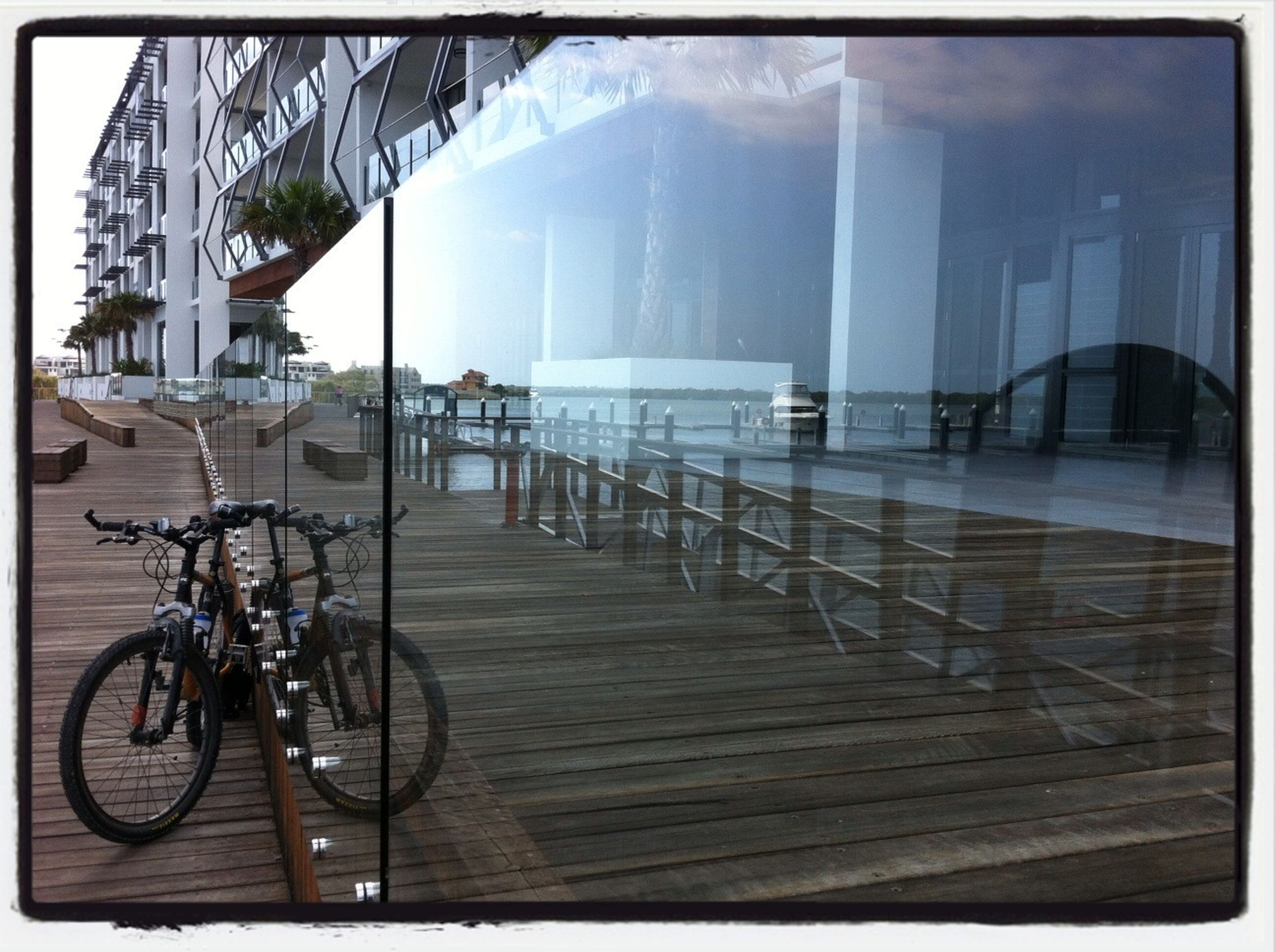 transfer print, auto post production filter, bicycle, transportation, mode of transport, land vehicle, built structure, panoramic, parked, railing, architecture, parking, sunlight, building exterior, stationary, water, absence, day, chair, outdoors