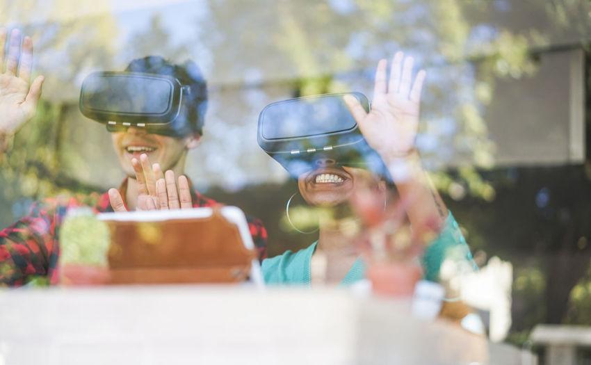 Smiling colleague looking through virtual reality simulators seen through window