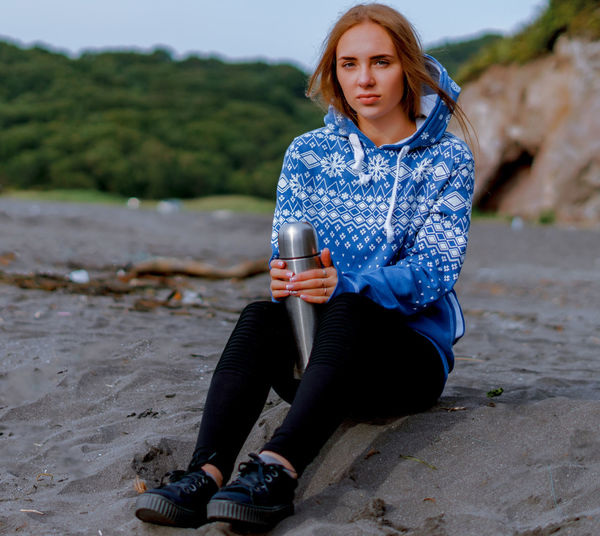 Portrait of young woman with insulated drink container sitting at beach