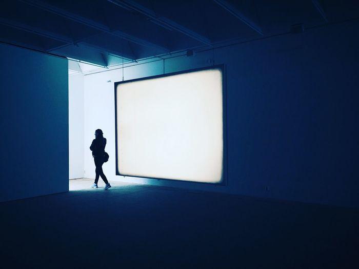 Woman walking by projection screen in board room