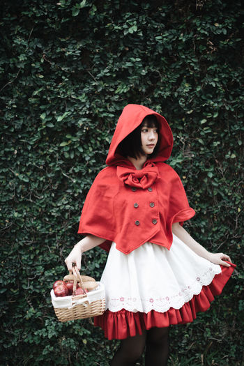Woman in little red riding hood costume holding basket while standing against plants