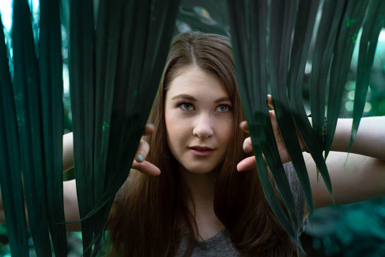 Portrait of beautiful young woman by leaves