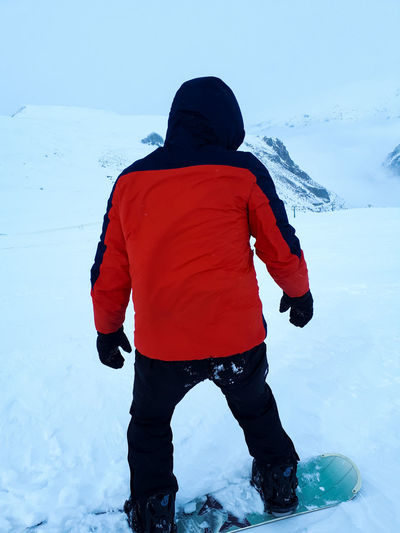 Rear view of boy standing in snow against sky