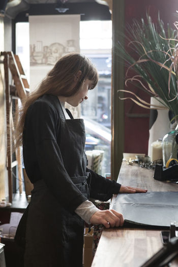 Side view of young woman looking at restaurant