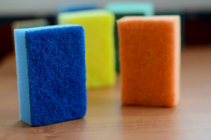 Close-up of multi colored cleaning sponges on table