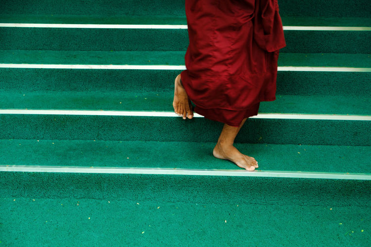 Low section of barefoot buddhist monk walking down on stairs. mandalay. amarapura. myanmar, burma