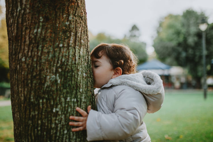 Side view of baby girl kissing tree trunk
