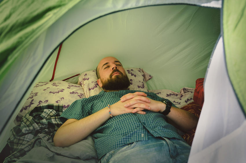 Young man sleeping in his tent Green Nature Pillow Tent Life Abstract Adult Beard Bed Bedroom Campinglife Domestic Room Eyes Closed  Facial Hair Linen Lying Down Lying On Back Real People Relaxation Resting Shirt Sleep Sleeping Tent Tent Camping Young Adult