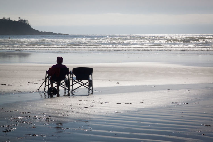 Rear view of man sitting on chair at beach