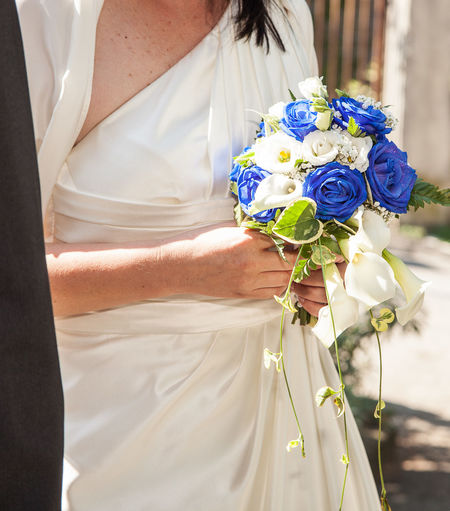 Midsection of bride holding flower bouquet during wedding