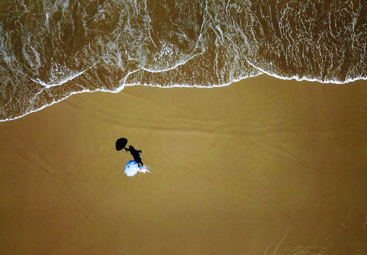 Aerial view of woman with umbrella standing at sandy beach