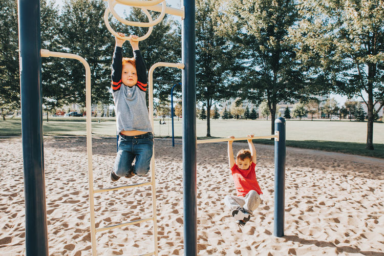 Brothers hanging on outdoor play equipment