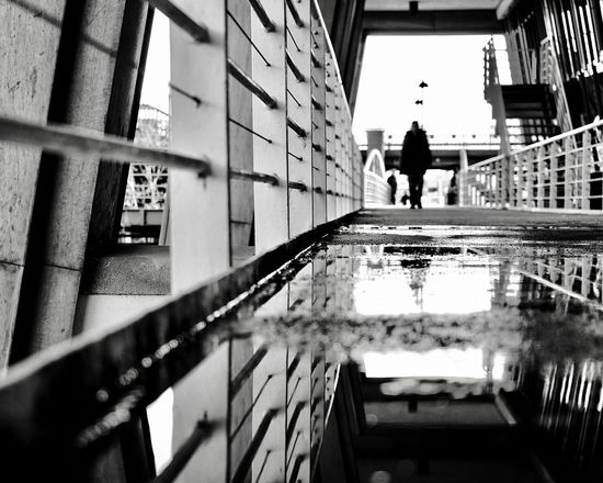 After the Rain Dramatic Angles depth of field Black And White Noir Et Blanc After The Rain Architecture Built Structure Reflection Building Exterior Day Building Lifestyles Railing Office Building Exterior Architectural Column Nature Outdoors Full Length City Water Men Walking People Incidental People The Street Photographer - 2018 EyeEm Awards