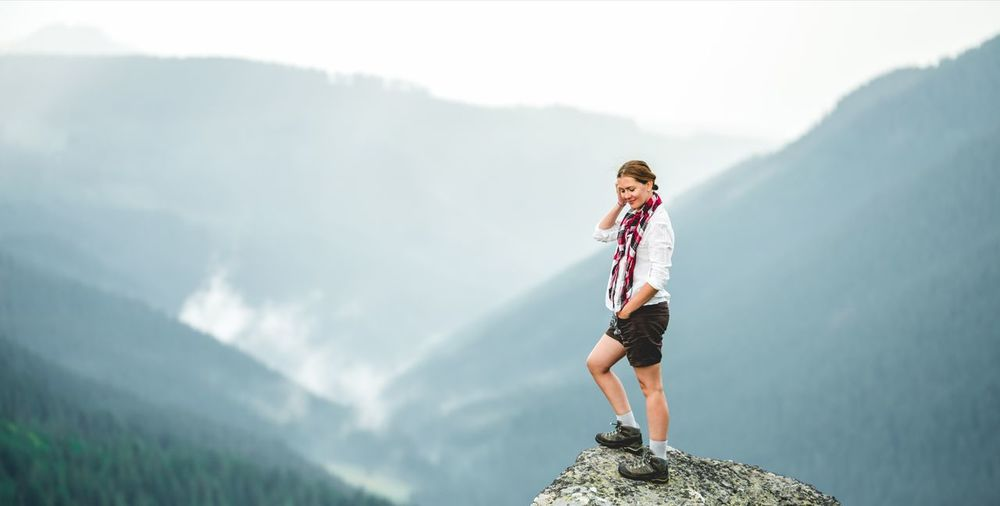 Full length of woman standing on rock against mountains