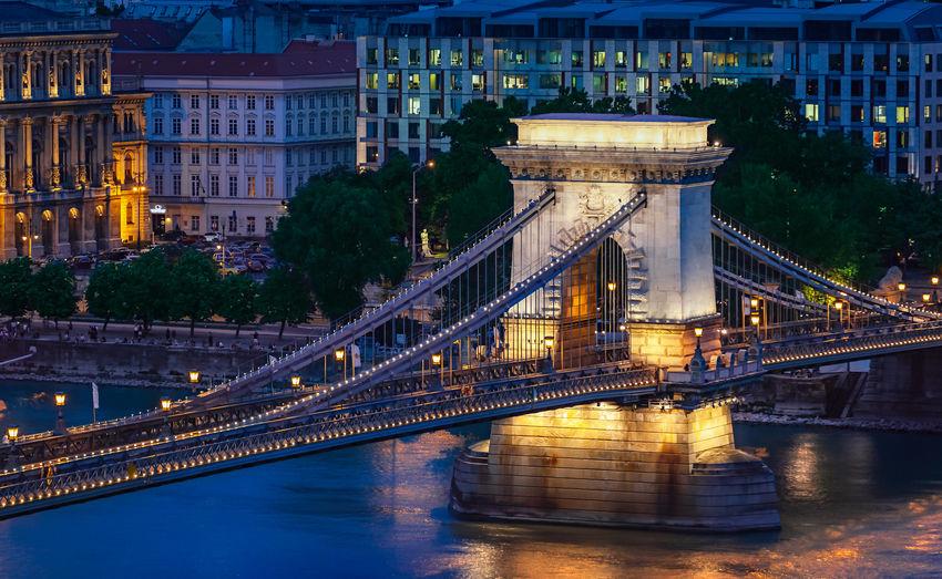 Illuminated szechenyi chain bridge over river at night