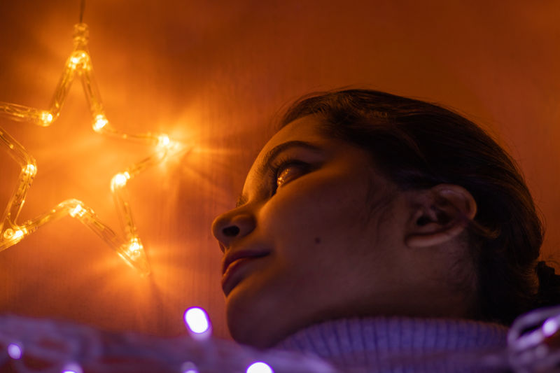 Close-up portrait of woman with illuminated lighting equipment at night