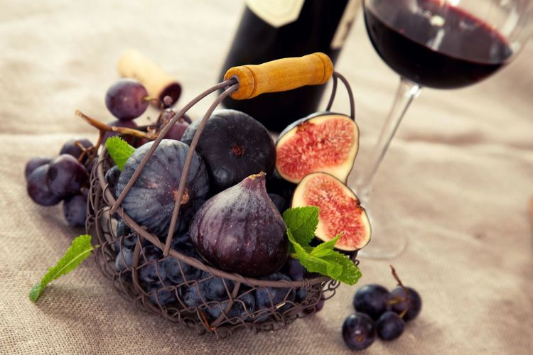 High angle view of figs and grapes in basket by red wine on table