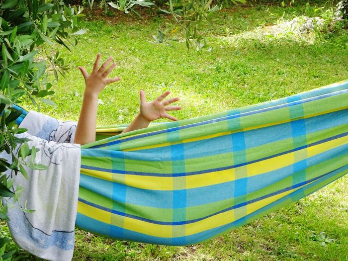 Relaxing Fun Hands One Person Leisure Activity Relaxation Human Body Part barefoot Real People Low Section Day Nature Body Part Sunlight Hammock Lying Down