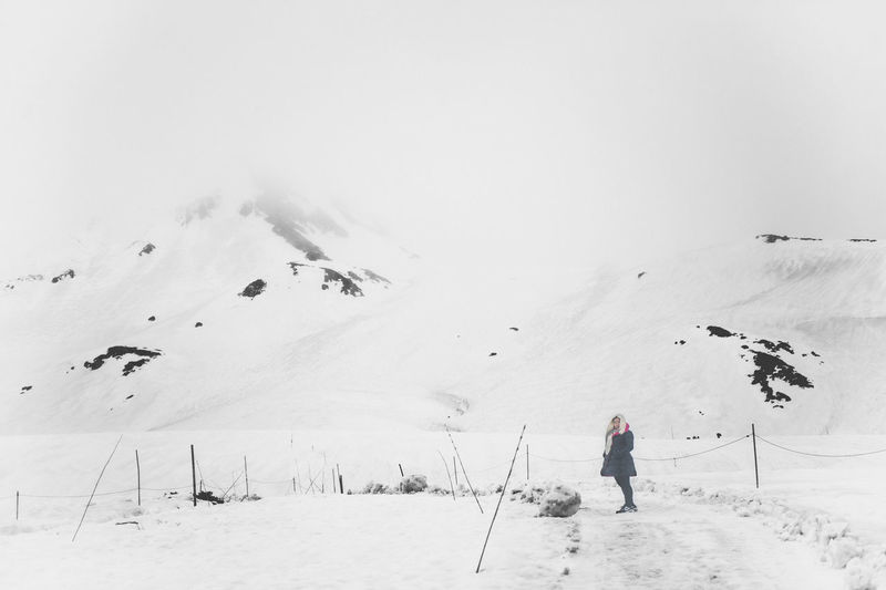 Woman standing on snowcapped mountain against