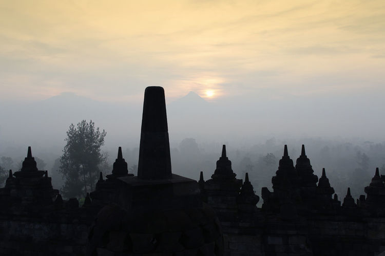 Silhouette Borobudur Temple with the mysteries forest surrounding during sunrise, Yogyakarta, Indonesia Ancient Borobudur Temple Java Yogyakarta Ancient Civilization Architecture Buddhism Built Structure Cloud - Sky Dawn Fog Forest History Mount Merapi Nature No People Place Of Worship Religion Religious Architecture Sky Spirituality Sunrise Sunset