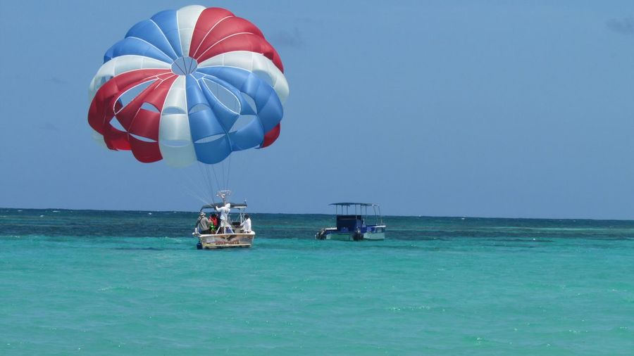 People Parasailing On Sea Against Clear Sky