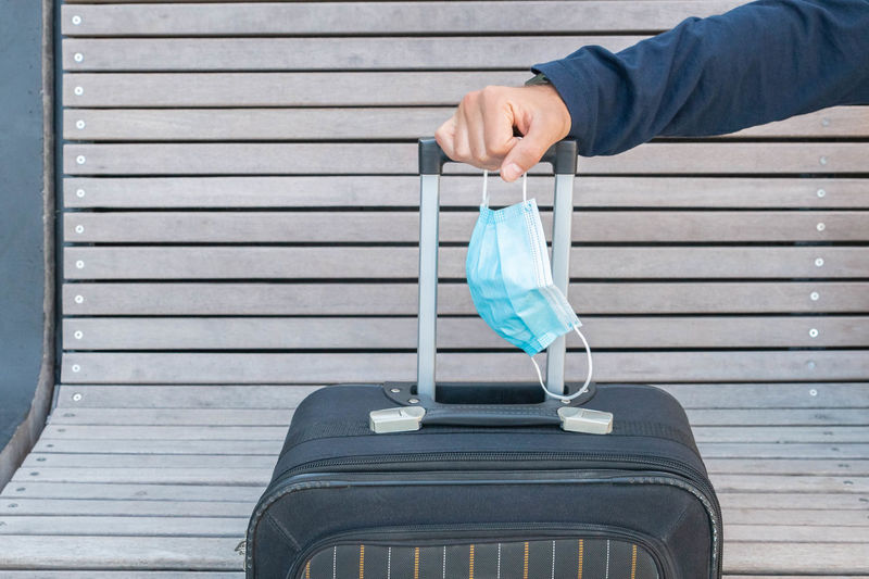Cropped hand of man holding mask and suitcase