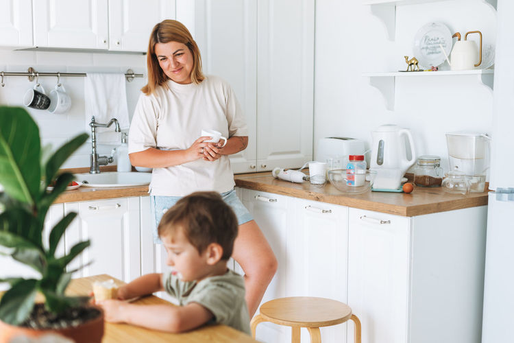 Young woman mother looking as her toddler boy son having breakfast at the table in kitchen at home