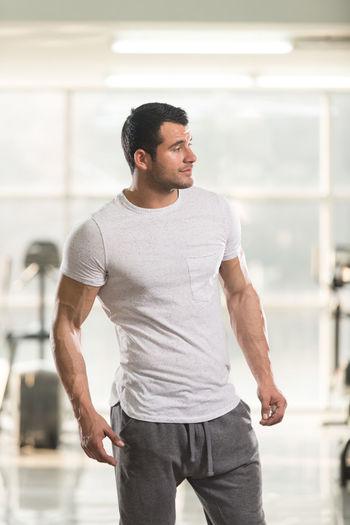 Muscular man standing in gym