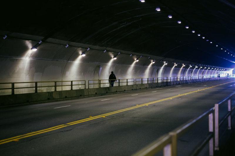 Man on illuminated road in stockton tunnel