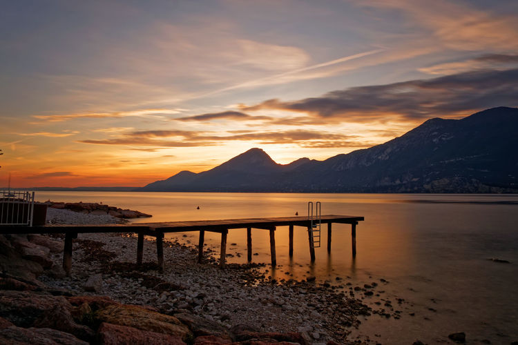 Beautiful long exposure sunset at Lake Garda Stockphoto Pier Lake Lake View Lake Garda Gardasee Fineartphotography Fine Art Long Exposure Skyporn Landscape Landscapes Wallpaper Sunsets Path Clouds Water Mountain Sea Sunset Beach Silhouette Summer Sunlight Reflection Romantic Sky Horizon Over Water Coastline Mountain Range Dramatic Sky Summer Road Tripping