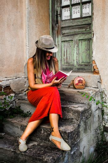 Full length of happy woman reading book on steps outside old house