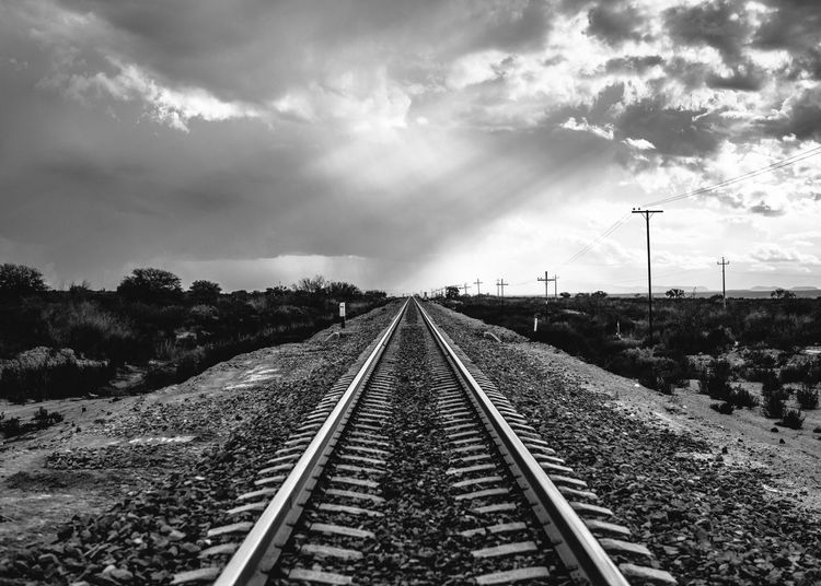 Railroad Track On Field Against Cloudy Sky