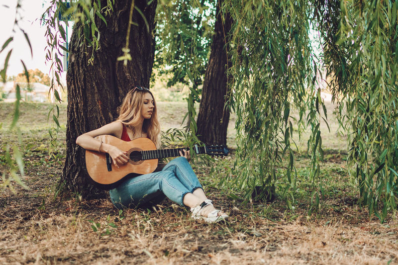 Full length of woman playing guitar while sitting under tree