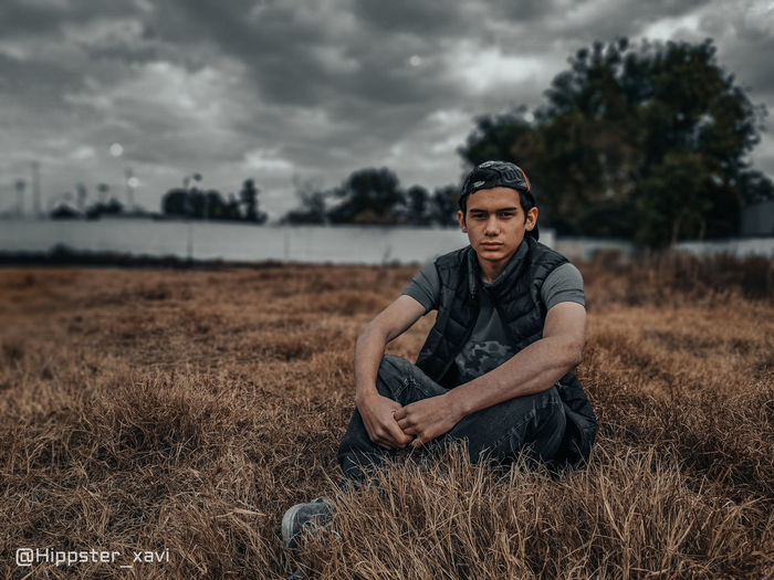 Portrait of young man on field against sky