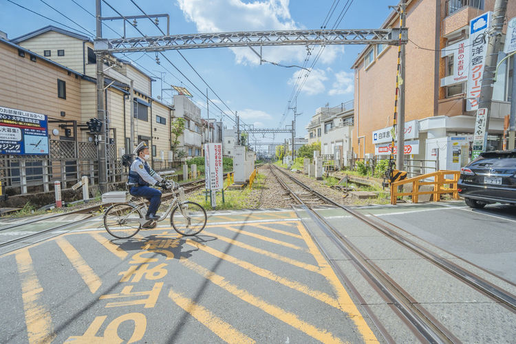 Cycling across the railroad Transportation Mode Of Transportation City Architecture Building Exterior Land Vehicle Built Structure Bicycle Street Road Sky One Person City Life Railroad Track Full Length Track Day Real People Riding Nature Outdoors Electricity  City Street