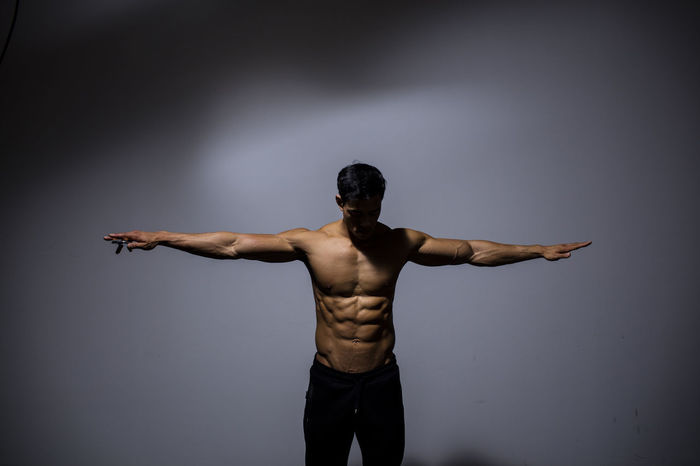 A male fitness model displaying his chiseled physique. Adult Arms Asian  Human Body Man Shirtless Vietnamese Abs Arms Spread Biceps Chiseled Fitness Fitness Model Fitness Training Looking Away From Camera Male Medium Shot Model Muscles Muscular Build Physique  Powerful Shoulders Six Pack Strong