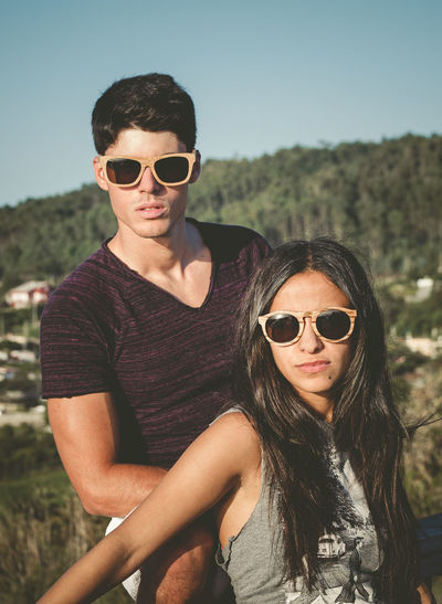 Young couple wearing sunglasses against sky