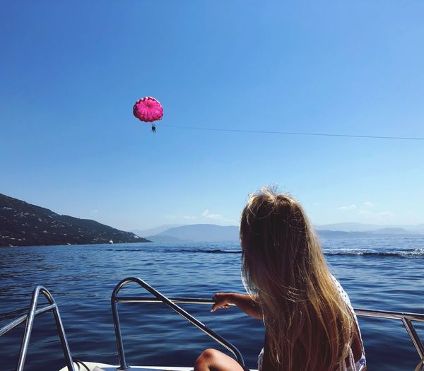 Water Sky Real People One Person Sea Lifestyles Leisure Activity Sunlight Clear Sky Transportation Adult Blue Beauty In Nature Nature Rear View Outdoors Women Day Balloon Hairstyle