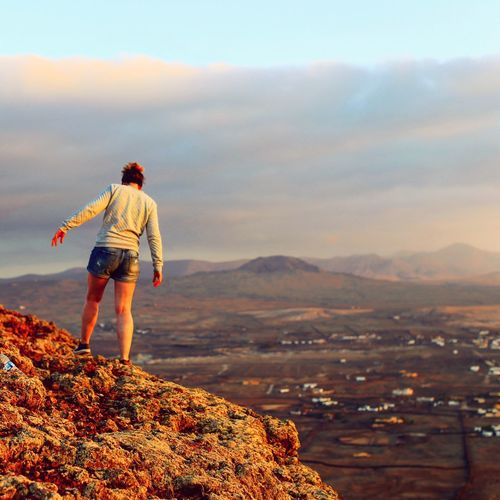 Rear view of man standing on mountain against sky