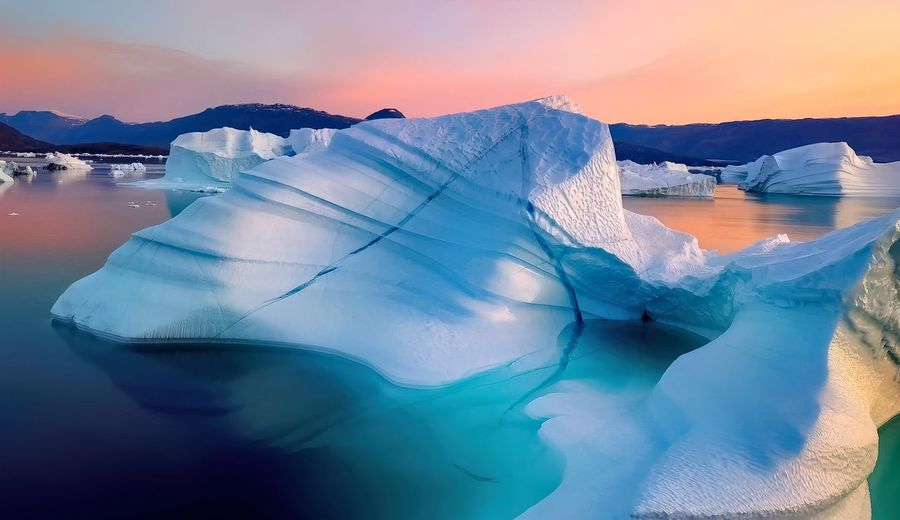 Iceberg floating in greenland fjord with sunset.