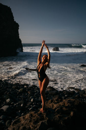 Swimwear - Tenerife Lifestyle Arms Raised Beach Beauty In Nature Exercising Full Length Horizon Over Water Human Arm Land Leisure Activity Lifestyles Nature One Person Real People Relaxation Exercise Rock Rock - Object Sea Sky Solid Sport Tenerife Water Young Women