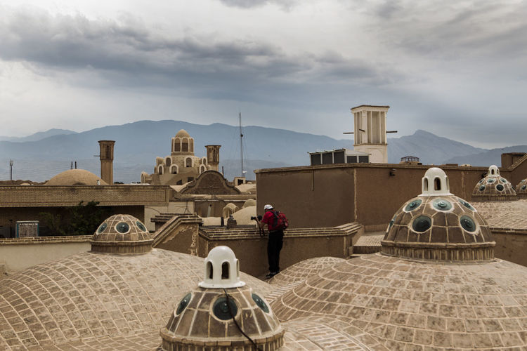 A tourist on the Roof of Soltan Amir Ahmad Bathroom and taking pictures with patience. Architecture Clothes Cloud - Sky Dress Iran Iranian Iranian People Kashan Mountain Mountain Range People Qajar Dress Real People Sky The Architect - 2017 EyeEm Awards The Great Outdoors - 2017 EyeEm Awards The Photojournalist - 2017 EyeEm Awards The Portraitist - 2017 EyeEm Awards Traditional Clothing Traditional Costume