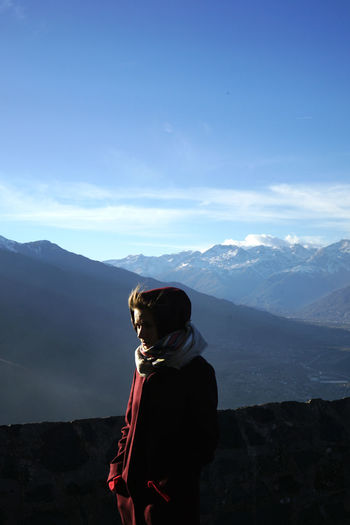 Woman looking at mountain against sky