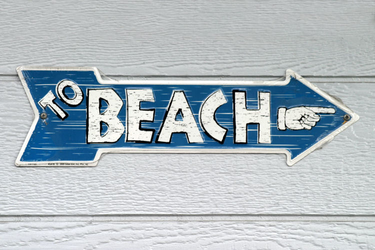 To Beach Sign with the text To Beach and a hand. Advertisement Arrow Away Beach Blue Direction Directional Escape Escapes Information Message Note Outdoor Path Promotion Recreation  Route Sign Summer Text Tourism Travel Vacation Way White