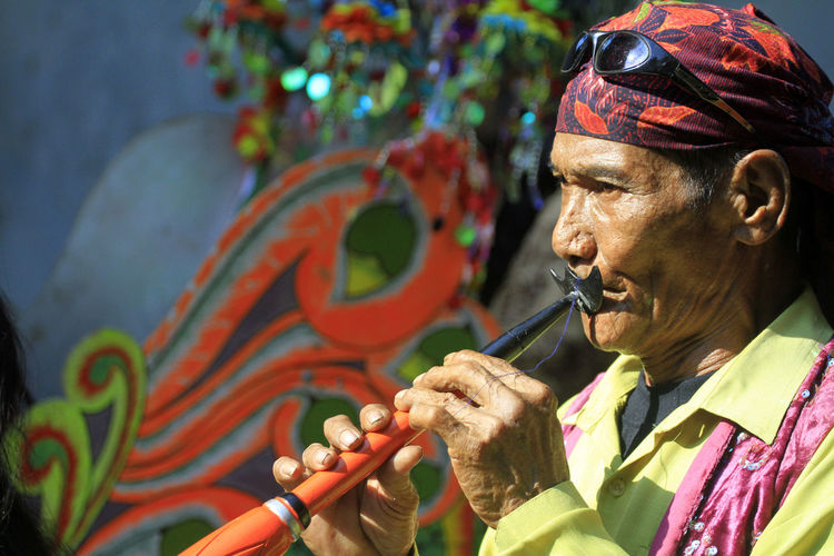 Close-up of mature woman playing musical instrument while standing outdoors