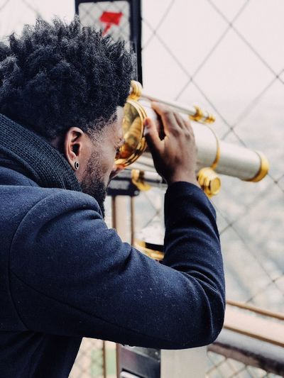 Side view of man looking through coin-operated binoculars