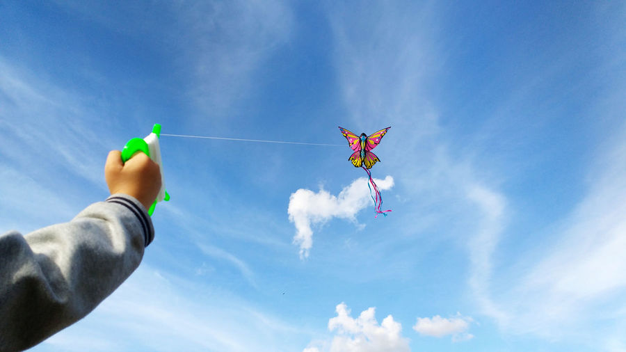 Low angle view of person flying kite