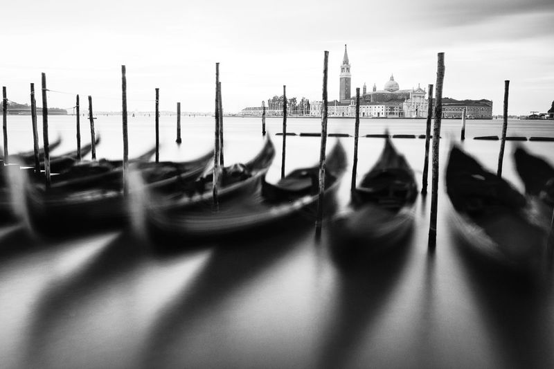 Gondolas moored by wooden post at grand canal against sky