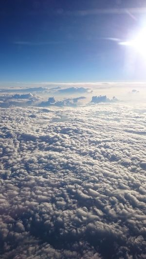 Aerial view of clouds over landscape against blue sky