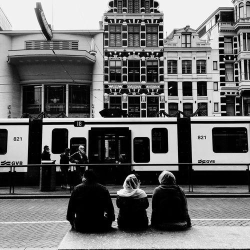 Rear view of people on street against buildings in city
